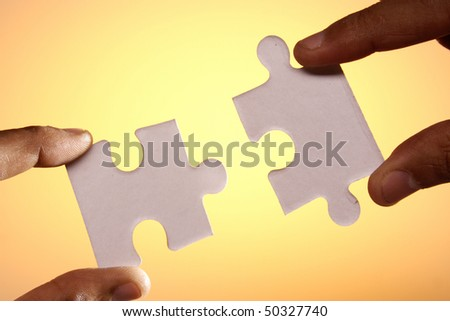 Joining Jigsaw puzzle pieces - stock photo