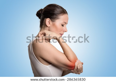 Joint inflammation indicated with red spot on female's elbow. Arm pain and injury concept. Closeup portrait woman with painful elbow on blue background  - stock photo