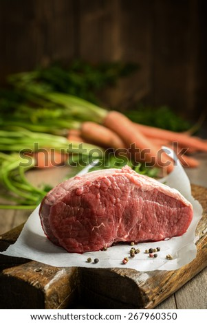 Joint of raw topside beef with carrots in the background - stock photo