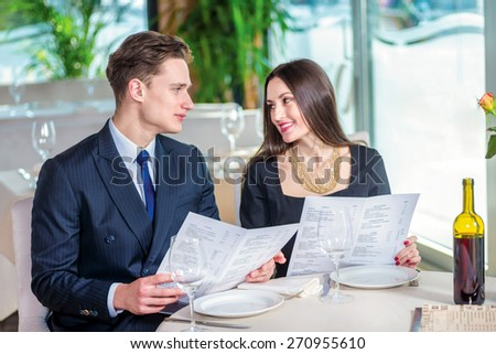 Joint selection of dishes on the anniversary. Romantic dinner in the restaurant. Young loving couple while visiting a restaurant menu holds in her hands and smiling at each other - stock photo