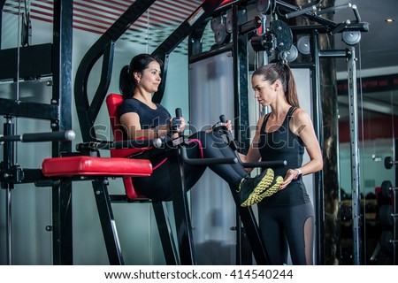 Joint training women. Trainer keeps track of exercise of the client. Sport exercises of the waist. - stock photo