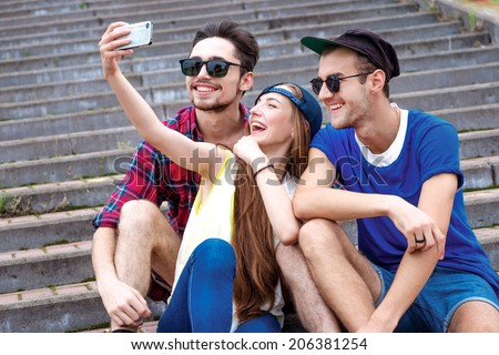 Joint walk friends. Young friends have fun together on the street and smile at each other. Funny guys make Selfie - stock photo