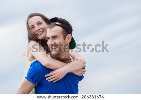 Joint walk loving couple. Girl hugging guy from behind
