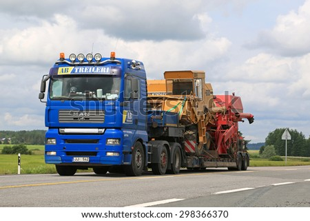 JOKIOINEN, FINLAND - JULY 18, 2015: MAN truck hauls combine harvesters on low floor trailer. Abnormal transport permit is required, if any dimension of the transport exceeds the free dimension limits. - stock photo