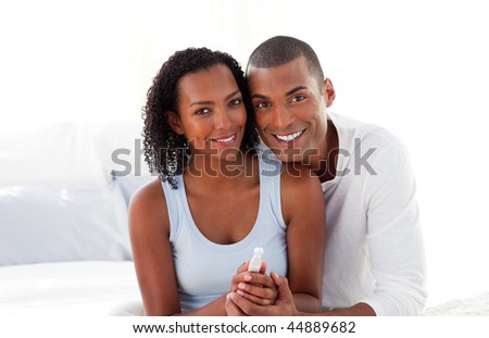 Jolly couple finding out results of a pregnancy test in the bedroom