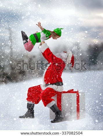 Jolly elf and Santa Claus play together. - stock photo