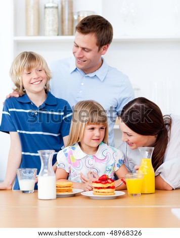 Jolly family eating breakfast in the kitchen at home - stock photo