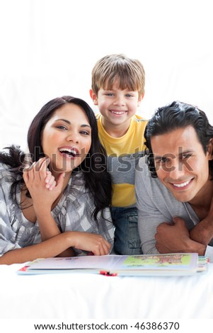 Jolly family reading book together lying on the floor - stock photo