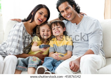 Jolly family relaxing sitting on the sofa in the living room - stock photo