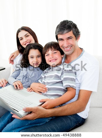 Jolly family using a laptop sitting on sofa at home