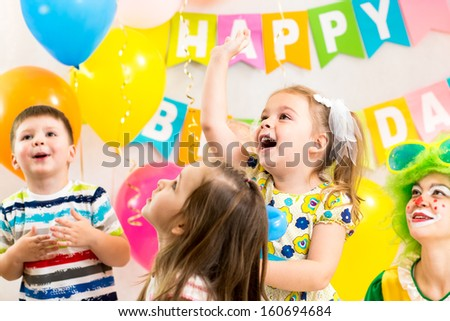 jolly kids group with clown celebrating  birthday party - stock photo