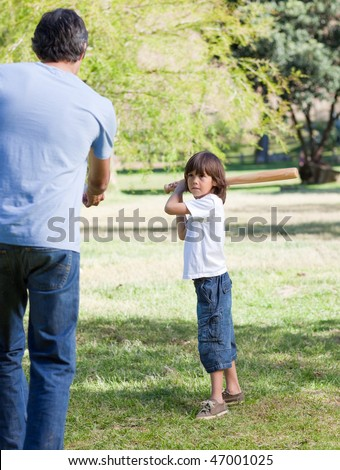 Jolly little boy playing baseball with his father in the park - stock photo