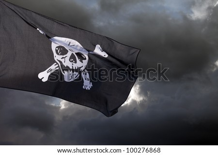 Jolly Roger (pirate flag) against storm clouds - stock photo