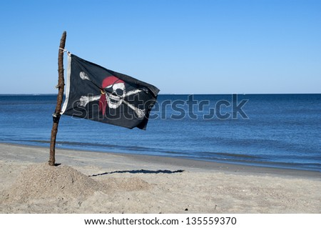 Jolly Roger Pirate flag blowing in the wind. - stock photo
