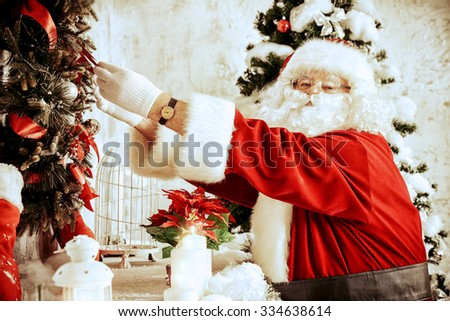 Jolly Santa Claus decorates the room for Christmas.