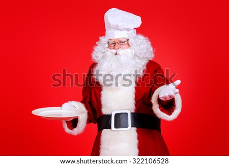 Jolly Santa Claus in a chef's hat holds a plate over festive red background. Copy space. Christmas treats.  - stock photo