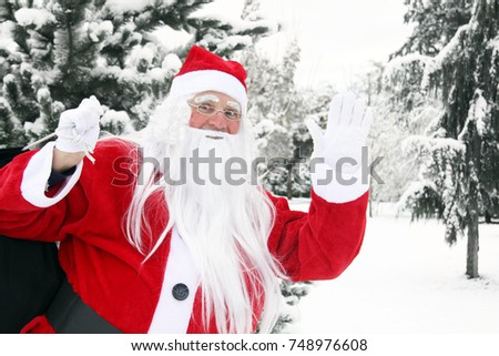 Jolly Santa Claus outside in the snow carrying his big bag of Christmas presents.