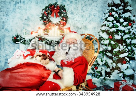 Jolly Santa Claus smoking a pipe and holding a sack with gifts. Christmas interior decoration. - stock photo