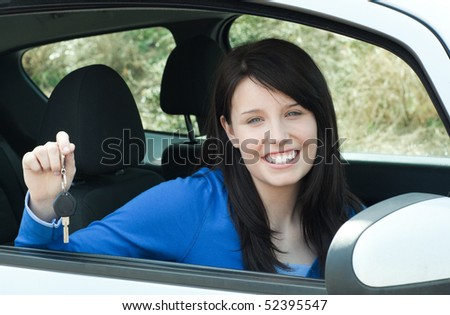 Jolly teen girl sitting in her car holding keys after bying a new car - stock photo