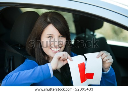 Jolly teen girl sitting in her car tearing a L-sign after having her driver's licence - stock photo