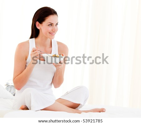 Jolly woman having breakfast sitting on her bed at home
