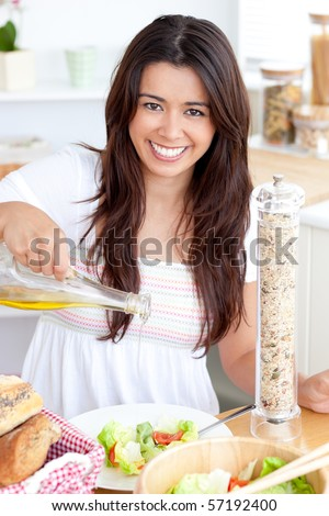 Jolly woman prepare a salad in the kitchen smiling at the camera