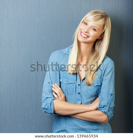 Jolly woman with arm crossed over the blue background
