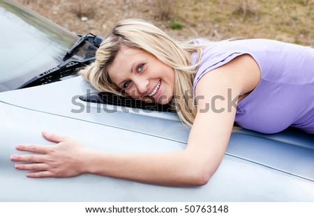 Jolly young female driver hugging her new car - stock photo