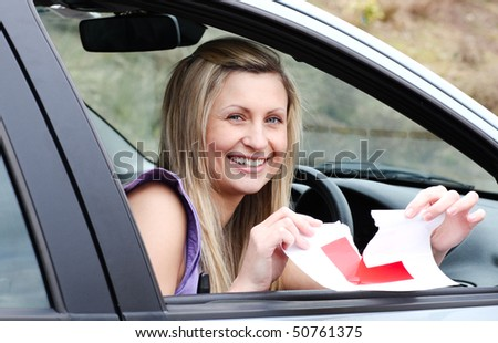 Jolly young female driver tearing up her L sign sitting in her car - stock photo