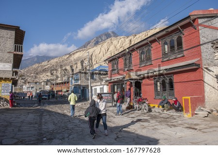 JOMSOM, NEPAL - NOVEMBER 11 : Unidentified tourists walking on the street of Jomsom Bazaar, Nepal on November 11, 2012