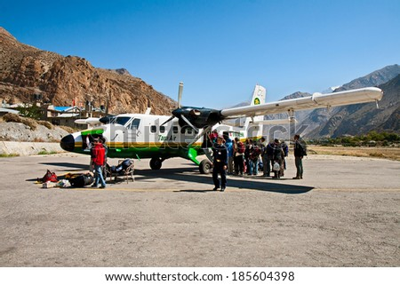 JOMSOM, NEPAL - OCTOBER 02, 2012 - Passengers boarding and loading of Luggage in the plane at the airport Jomsom - stock photo