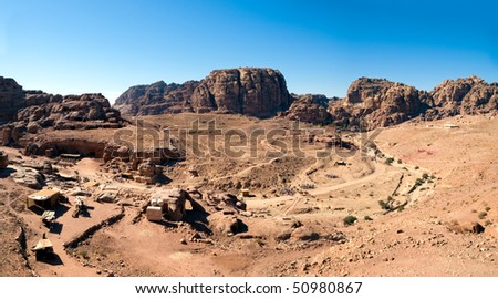 Jordan Petra desert panorama with a toms in the distance and blue sky above. Temple and tombs visible