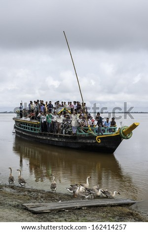 JORHAT, INDIA - AUGUST 23:  Overcrowded passenger ferry arrivers at Nimati Ghat from Majuli island having crossed the Brahmaputra on August 23, 2011 at Jorhat, Assam, India.