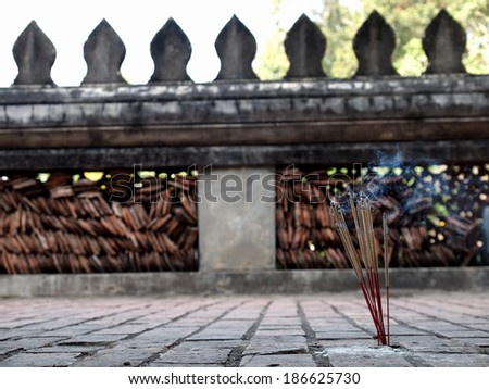 joss sticks smoke on the stone ground floor of a temple corridor terraces with temple wall with typical buddhism decorative stone leaf form ornament in the background in Vientiane, Laos - stock photo