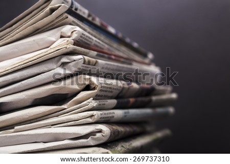 Journalism. Stack of newspapers on black background - stock photo