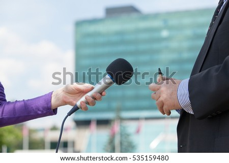 Journalist interviewing business person, corporate building in background