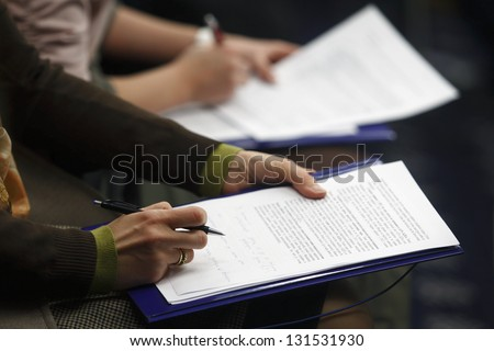 Journalist is reading press material during a conference - stock photo