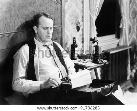 Journalist sitting on his bed with a typewriter, typing - stock photo