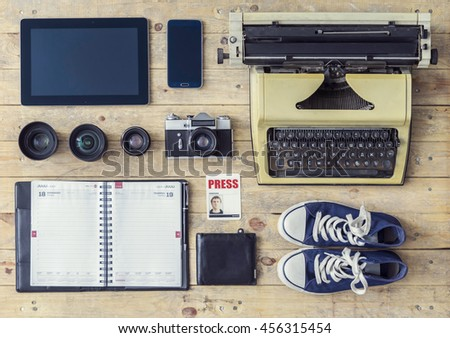 Journalistic equipment: typewriter, tablet, phone, camera, lenses, album, glasses and different objects. Past and nowadays concept. Freelancers outfit.