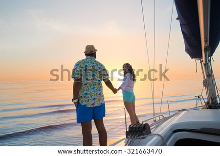 Journey around the world on a yacht. Love story. Honeymoon trip on a sailing yacht. Yacht at sunset. Date of guy and girl on a yacht. Trip around the world. - stock photo