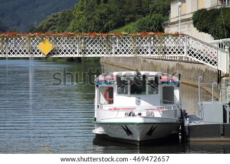 Journey boat on the river under pedestrian bridge with flowerbeds in germany