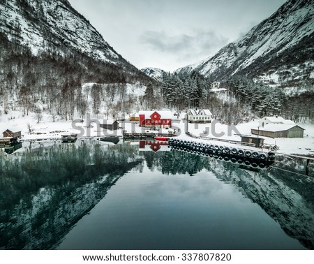 journey through fjord. red house on a background of the rocky mountains - stock photo
