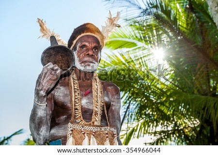 JOW VILLAGE, ASMAT, NEW GUINEA, INDONESIA -JUNE 28: Asmat tribesman with drum.The In the village of Asmates goes preparation for of a ceremony of Doroe. June28, 2012 in Jow Village, Asmat, Indonesia  - stock photo