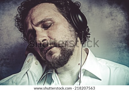 Joy, listening and enjoying music with headphones, man in white shirt with funny expressions