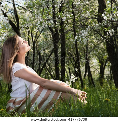 Joy spring sun. Attractive young woman sitting with eyes closed in a lush garden on the grass. Spring mood - stock photo