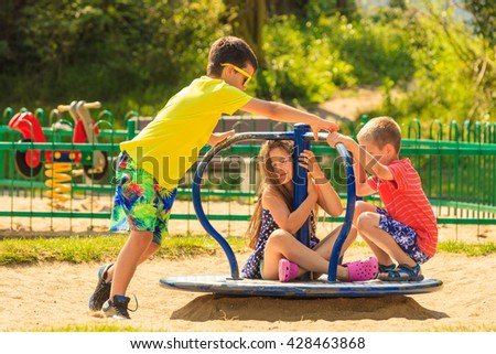 Joyful active childhood. Playful kids playing on playground. Children having fun in summer. Young tourists spending actively time. - stock photo