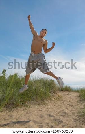 Joyful African American Male Jumping Outdoor in Summer - stock photo