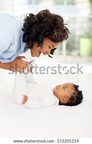 joyful african mother playing with baby infant - stock photo