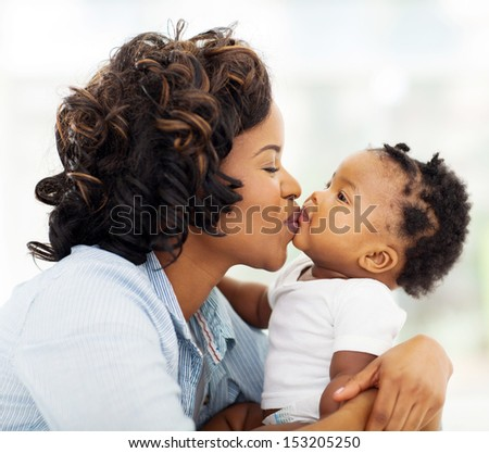 joyful and caring mother kissing her daughter at home - stock photo