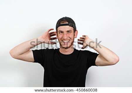 Joyful and Smiling Happy Young Adult Male in Dark T-Shirt and Baseball Hat Worn Backwards - stock photo